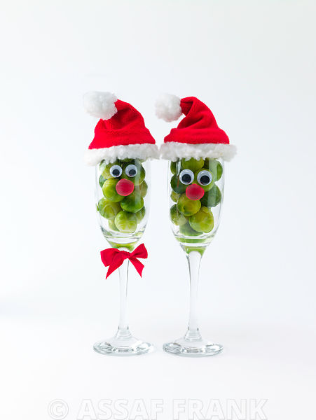 Santa face on wine glasses filled with brussel sprouts