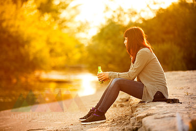 Young woman drinking beer on a riverbank, Osijek, Croatia