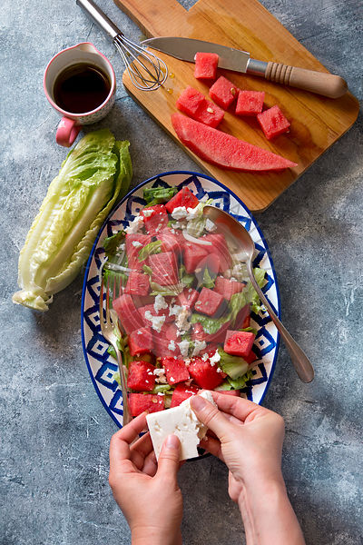Watermelon lettuce salad with feta cheese and balsamic dressing on a plate.Top view