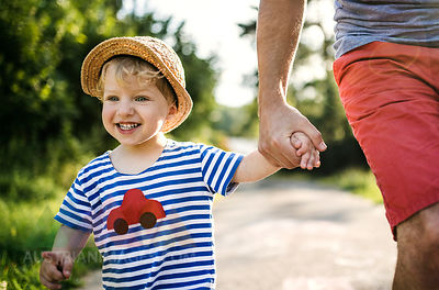 Portrait of laughing toddler walking on father's hand