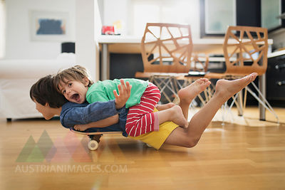 Two brothers at home lying on skateboard together having fun