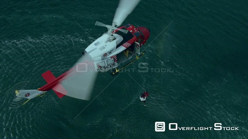 Aerial of two men being airlifted out of the sea by a rescue helicopter Cape Town Western Cape South Africa