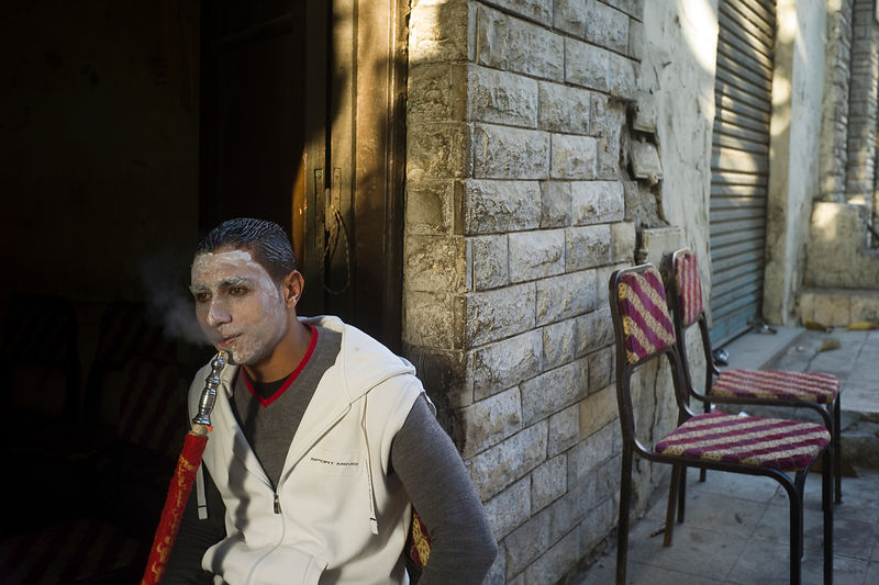 Egypt - Cairo - A young man smokes a shish pipe in a coffeshop or ahwa whilst wearing a face pack so that he can look at his ...