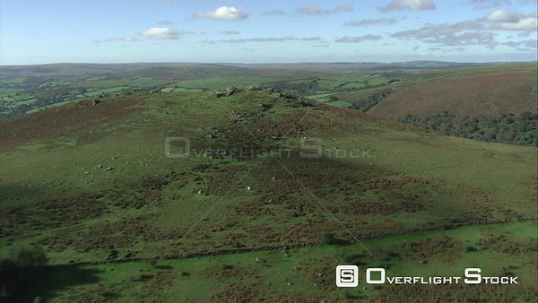 Aerial view tracking over Chinkwell Tor to WidecombeintheMoor, Dartmoor National Park, Devon, England, UK, October 2015.