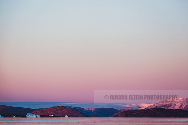 The Greenlandic icecap at sunset in a very pink glow as seen from Uummannaq