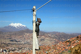 Dummy strung up on street lamp as a warning to thieves, Mt Illimani in background, La Paz, Bolivia