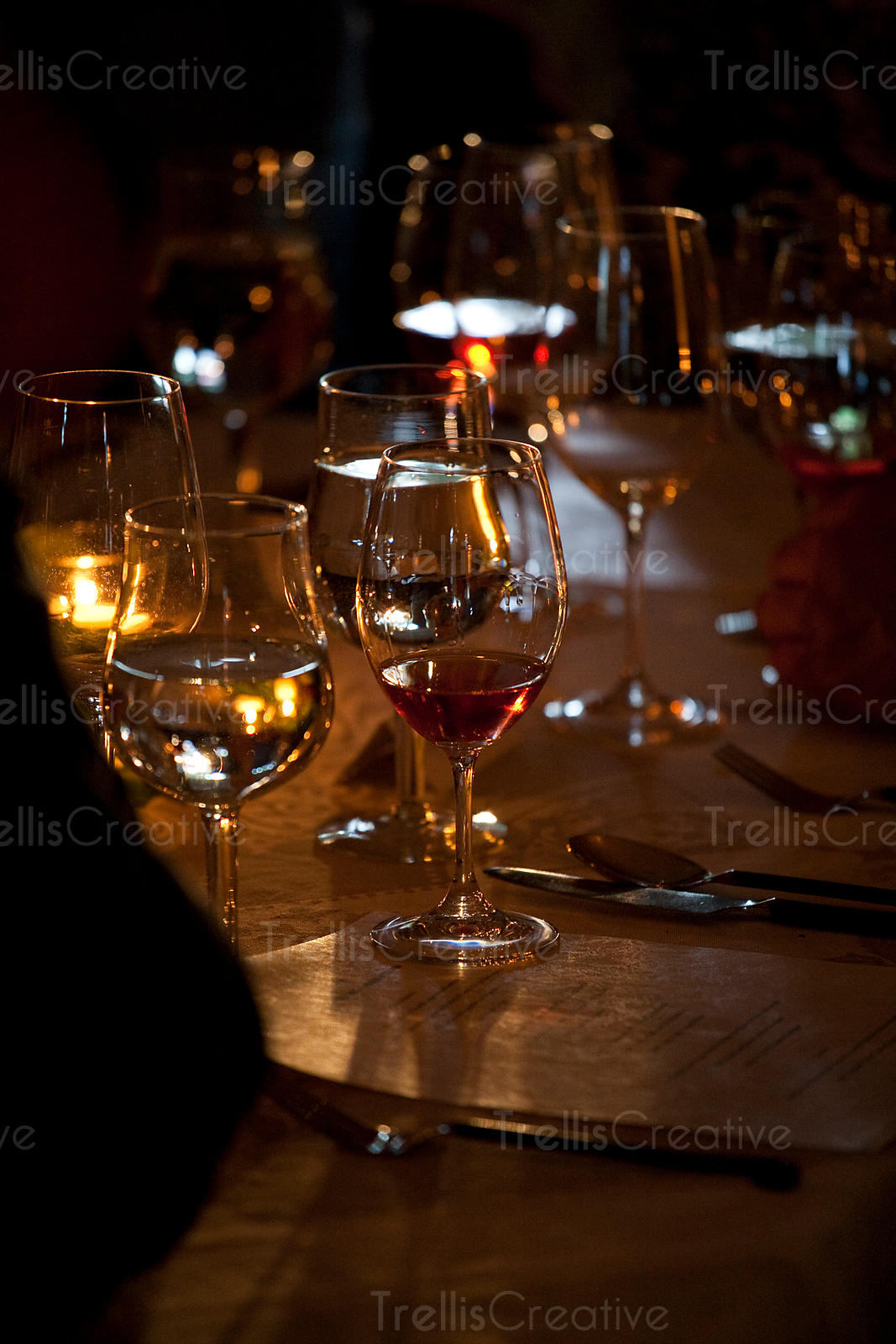 Wine glasses on an elegant candle lit dinner table