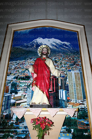 Statue of Jesus in front of photo of city and its guardian peak Mt Illimani, San Pedro church, La Paz, Bolivia