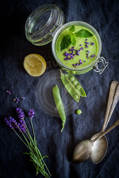 Green gazpacho in jar with peas and lavender on gray towel background with vintage spoons. Top view