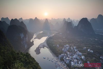 Sunset over river with karst peaks, China