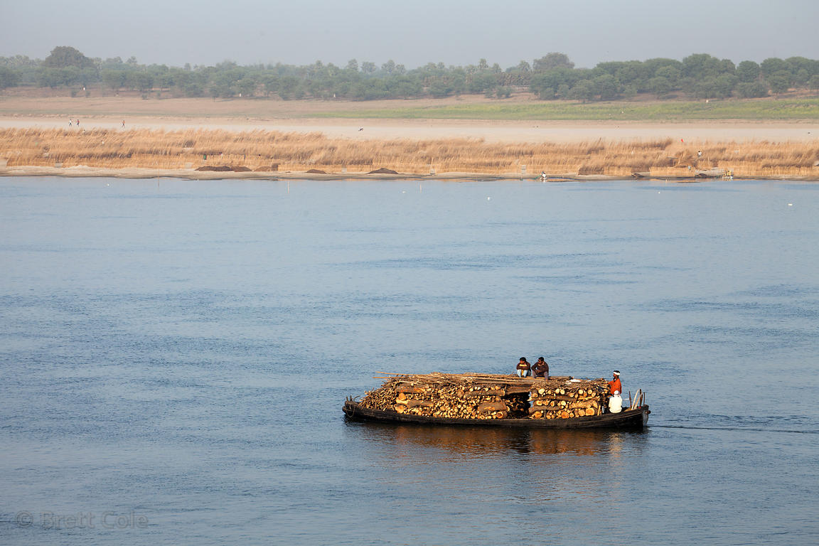 A boat on the Ganges River carries firewood to Harish Chandra Ghat crematoreum (Burning Ghat), Varanasi, India.