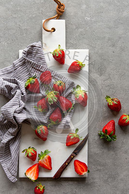 Fresh strawberries in striped kitchen towel on white marble board over grey concrete background
