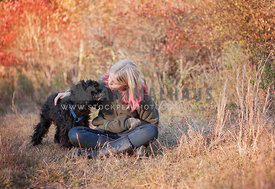 Sitting Blonde girl kissing black cockapoo dog wearing a harness in a fall colored field