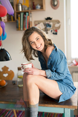 Portrait of laughing woman sitting on kitchen table with coffee mug