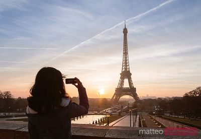 Woman taking a photo of the Eiffel tower, Paris, France