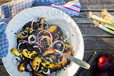 Bowl with lentil and fruit salad on a wooden garden table with kitchen towel. Top view