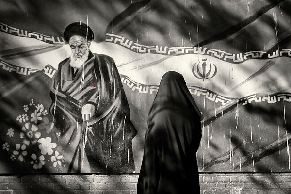 Woman in a Chador Walking Past a Mural of Ayatollah Khomeini