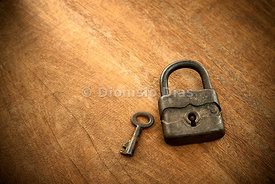Old padlock with key next to a wooden background