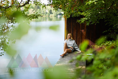 Relaxed woman sitting on wooden jetty at a remote lake