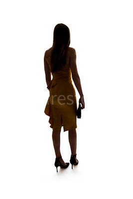 A mystery woman wearing a party dress, in silhouette, walking away – shot from eye level.