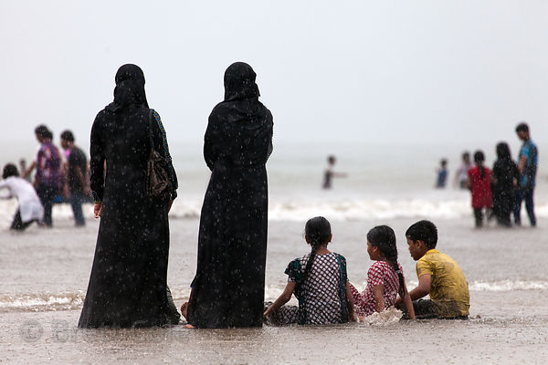 Muslim women and children in the Arabian Sea during a monsoon rain, Juhu Beach, Mumbai, India.