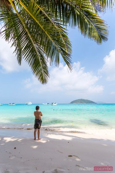 Boy looking at view on tropical beach, Thailand