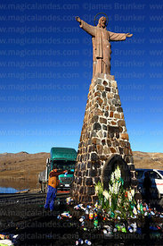 A man sprinkles beer as an offering to Pachamama at base of Christ statue, La Cumbre, Cordillera Real, Bolivia