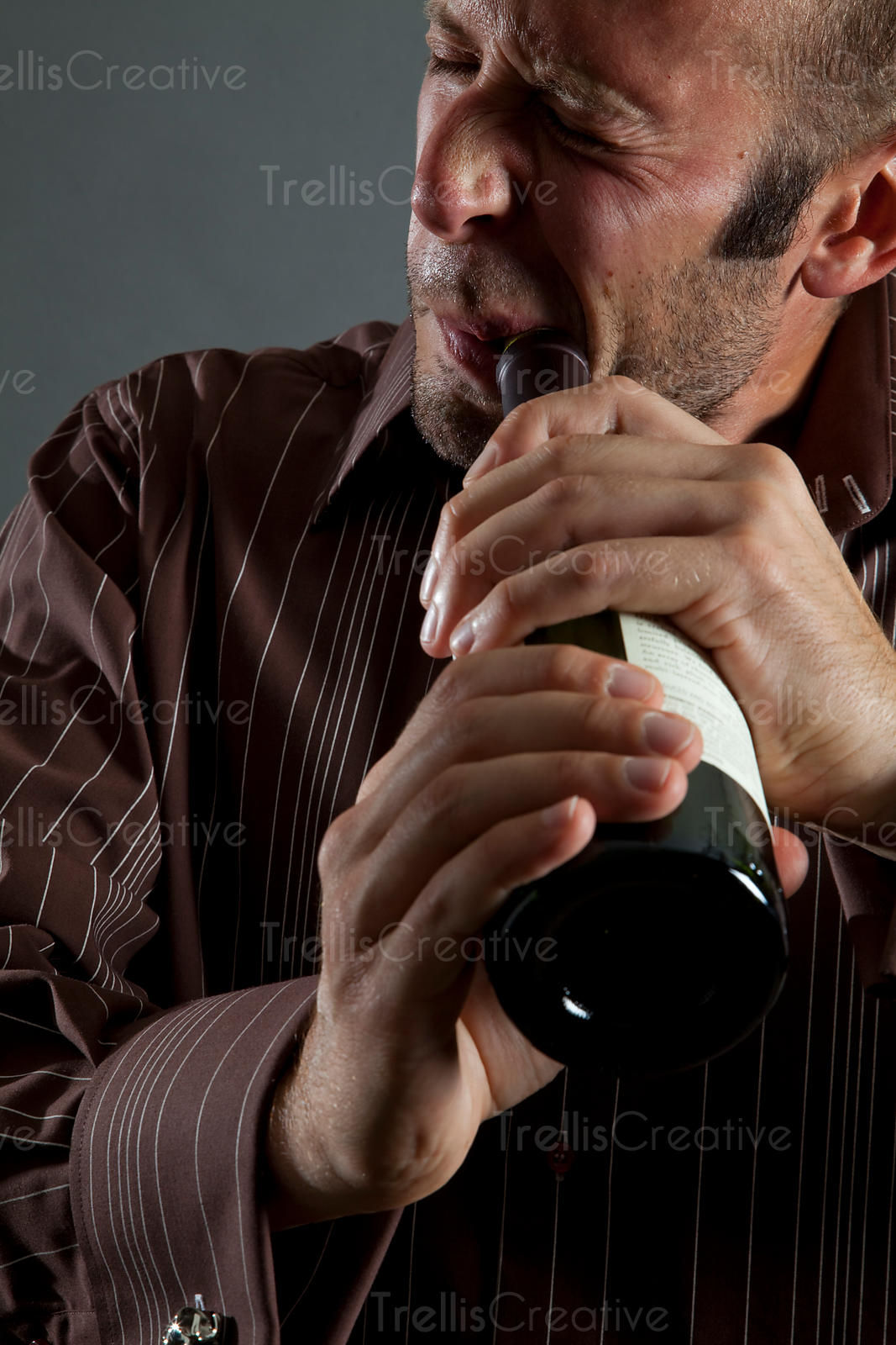 Man pulling cork from wine bottle with his teeth