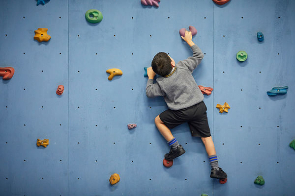 A child using a climbing wall in school
