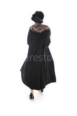 A vintage 1920s - 1930s woman in a long black coat, hat and fur – shot from eye level.
