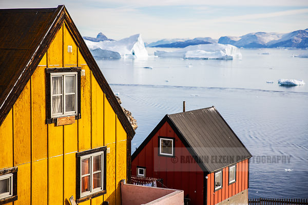 Typical Greenlandic wooden houses with beautiful icebergs in the fjord in the background