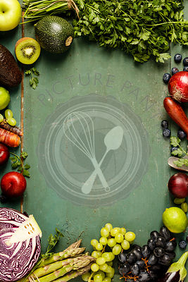 Assortment of raw organic fruits and vegetables: eggplants, onions, berries, carrots, grapes, cabbage, avocado, plums over ru...