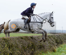Charlotte Bell jumping a hedge on Greenall's