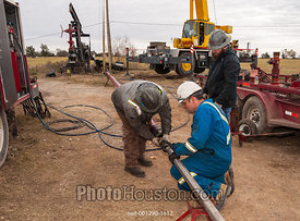 Man attaching drill bit to bottom hole assembly of oil well