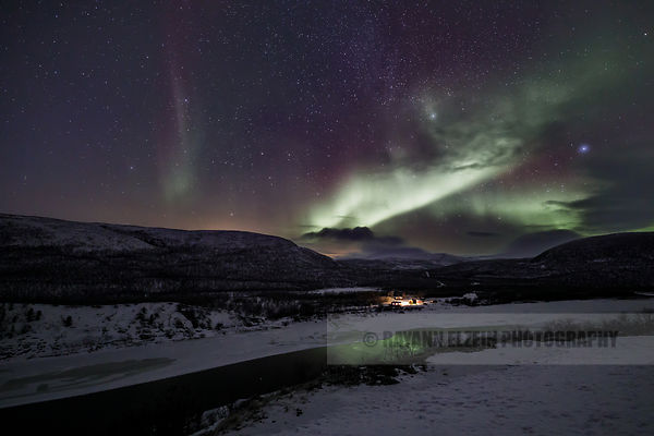 Aurora reflecting on an unfrozen part of the Teno River near Utsjoki