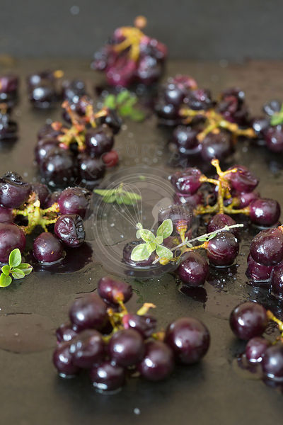 small bunches of black grapes on dark metal tin oven roasted with thyme herbs and balsamic vinegar seasoning