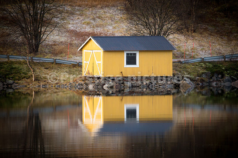 Waterside Yellow building reflecting in the mirror-like waters of the fjord