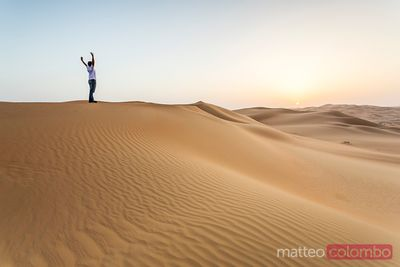 Lonely man on sand dune in the desert contemplating sunrise