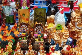 Statues of chickens, smiling buddha and golden $100 bills for sale on stall, Alasitas festival, La Paz, Bolivia
