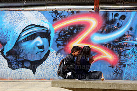 Young couple sitting on concrete bench in Plaza Camacho, La Paz, Bolivia