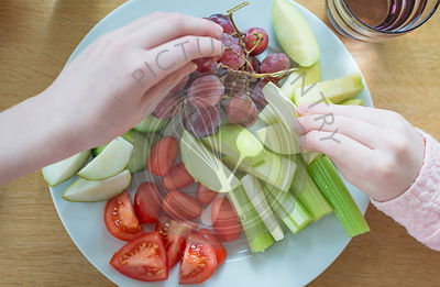 Hands taking fruit from a plate of snack food.