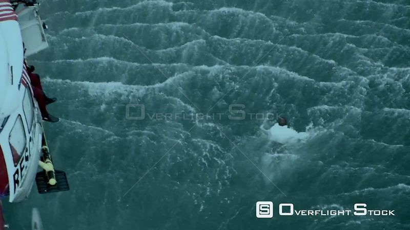Aerial zoom in to a man struggling in the sea while a rescue helicopter hovers above Cape Town Western Cape South Africa
