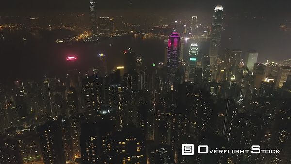 Hong Kong Skyline and Victoria Harbour at Night. Aerial View. Drone is Flying Sideways. Camera is Tilting Up. Reveal Shot.