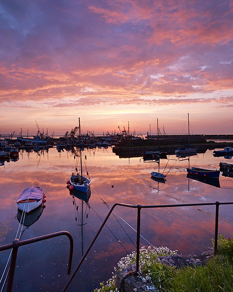 Dawn twilight with underlit clouds and moored boats in the harbour of the fishing port of Newlyn in Cornwall, UK.