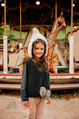 Portrait of smiling little girl wearing fur hat standing in front of children's carousel