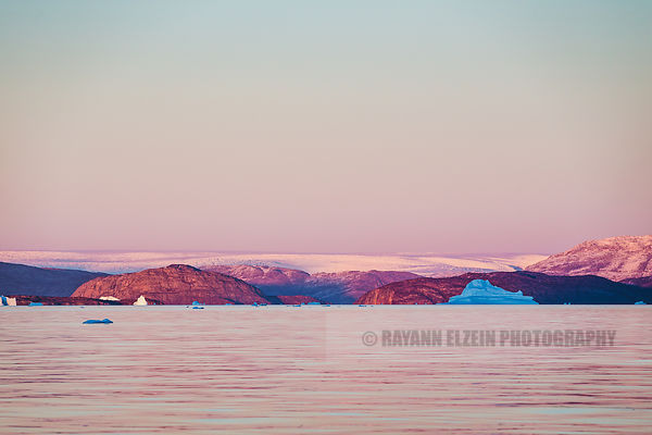 The pink glow of the sunset reflects on the Greenlandic icecap in the background