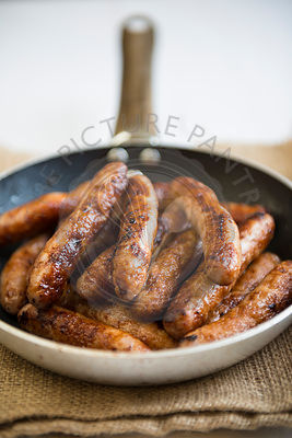 Frying pan full of sausages.