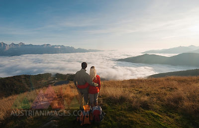 Austria, Steiermark, Reiteralm, Couple of hikers admiring view over clouds, rear view