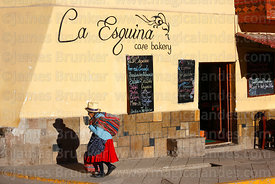 Elderly Quechua woman walking past La Esquina tourist cafe, Ollantaytambo, Sacred Valley, Peru