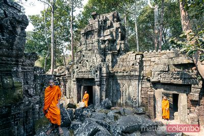 Buddhist monks inside temple ruins, Angkor, Cambodia